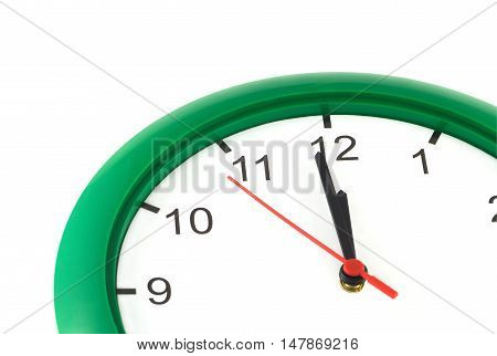 Fragment of big wall clock with green case shows almost twelve o'clock isolated on white closeup