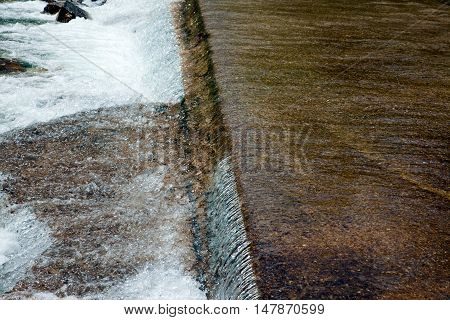 Water flowing swiftly over a concrete bridge.