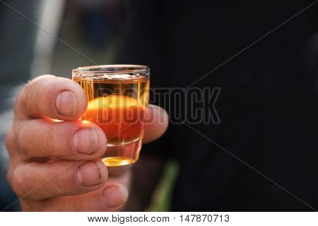 dirty man's hand holding a shot glass with orange alcohol drink background with copy space fades to black