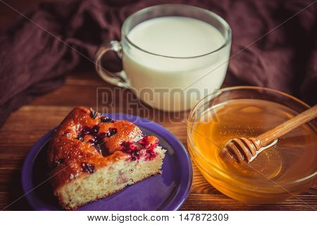 Fruit cake honey and milk. Petite fresh flavored dessert. A delicious fruit tart with milk and a mod on a wooden table. Aromatic cake with fresh fruit fragrant and fresh honey farm milk on the table.