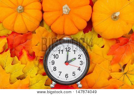 Fall Time Change Some fall leaves and a pumpkins with a alarm clock