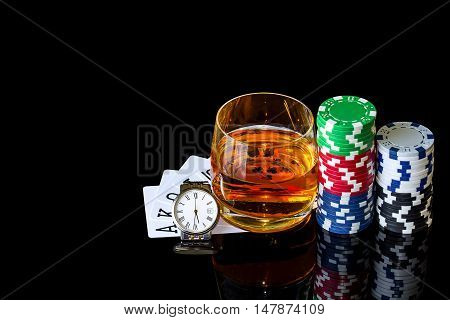 Cards with chips to play poker and tumbler whiskey with watch