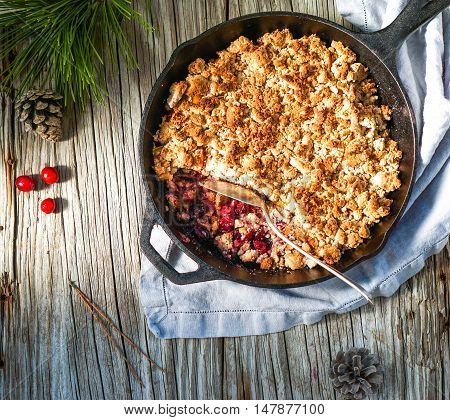 Winter Berry Crumble in an iron pan on wood rustic background.