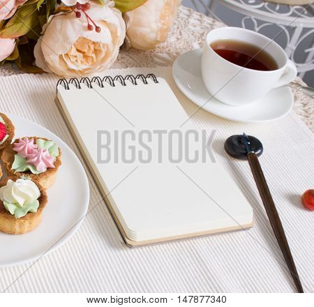 Mockup photography with flowers notebook and pen with nib. Desktop workplace designer artist painter perspective view. Modern trend template for advertising.
