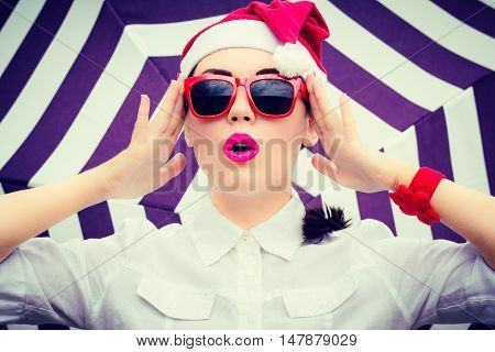 Portrait of a funny girl in Santa Claus hat and red sunglasses with bright painted lips next to striped background