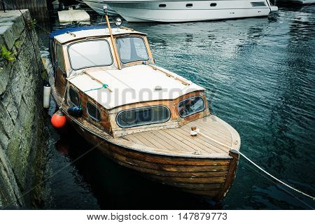 Old wooden row boat on water in Norway