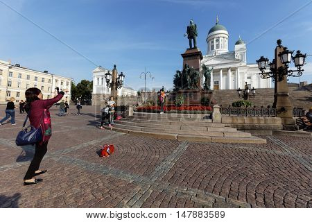 HELSINKI, FINLAND - AUGUST 21, 2016: Chinese tourists make photos against the statue of Alexander II on Senate square. It was built to commemorate his re-establishment of the Diet of Finland in 1863