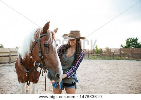 Cheerful cute young woman cowgirl standing and taking care of her horse in village