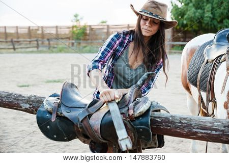 Beautiful young woman cowgirl in hat preparing saddle for riding horse