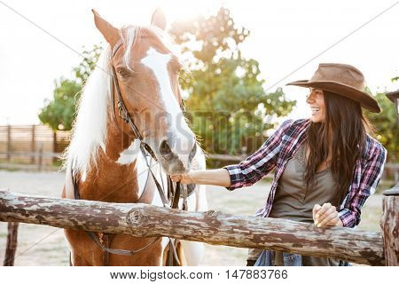 Smiling attractive young woman cowgirl walking with horse on farm
