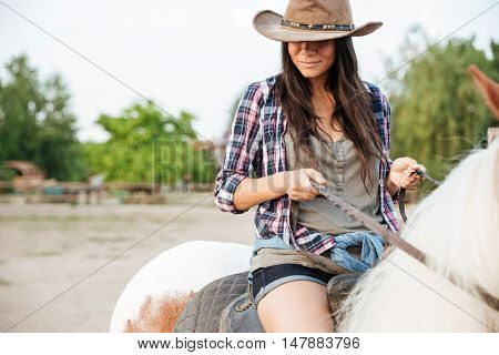 Closeup of beautiful young woman cowgirl sitting and riding horse in village