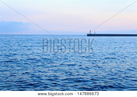 Mediterranean Sea at Genoa port with small beacon at sunset Italy