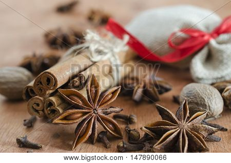 Spices for mulled wine. Closeup of cinnamon sticks anise stars and cloves on wooden background. Selective focus. Macro with shallow dof.