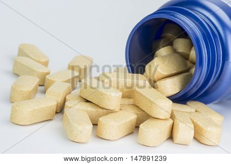 Collection yellow tablets from a fallen blue medicine jar