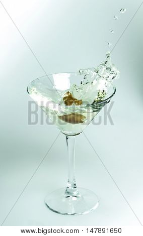 Green Olive Splashing in a Cocktail Glass