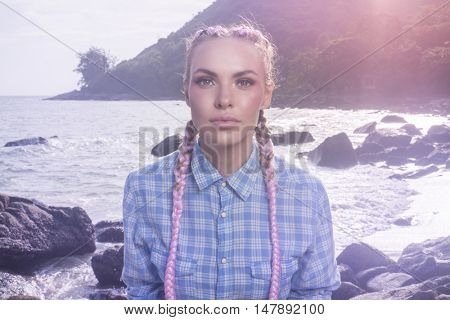 Portrait of young pretty girl with pink plaits wearing blue checked shirt looking into the camera while sitting on the rock during summer day over sea and sky background