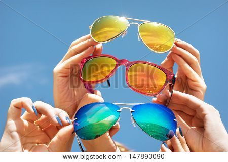 Hands hold three sunglasses on blue backdrop of sky
