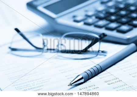 Pen, Eyeglasses and Calculator on Financial Figures