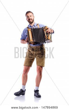 Handsome young man in traditional bavarian clothes playing accordion. Oktoberfest. Studio shot on white background, isolated.