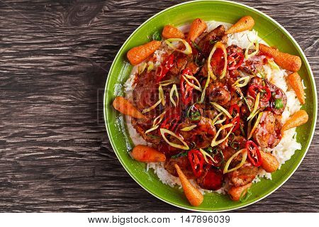 takeawy classic pork on rice with fried in sticky souce carrots, sprinkle of chillie and spring onion