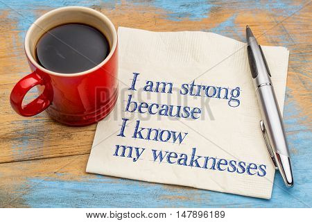 I am strong because I know my weaknesses - handwriting on a napkin with a cup of espresso coffee