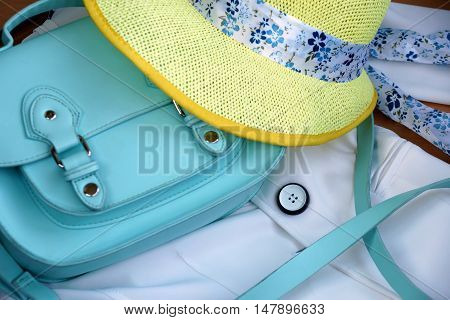 Women turquoise bag and yellow hat on a white jacket