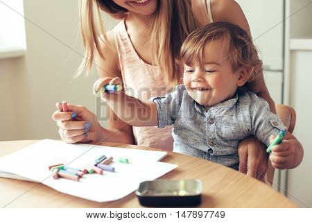 Mother playing with her 1,4 years old son, drawing together