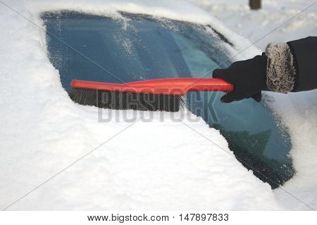 Woman's hand in black garment brushing snow from car windshield on winter day