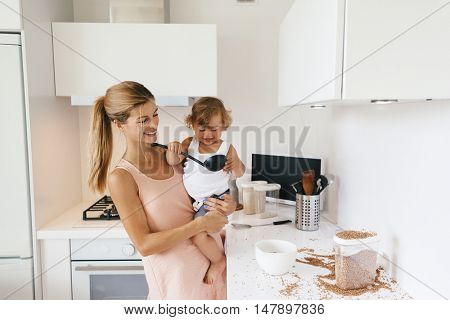 Mom with her 1,4 years old child cooking in the white kitchen interior