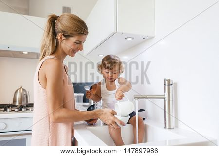 Mom with her 1,4 years old child washing dishes in the white kitchen interior