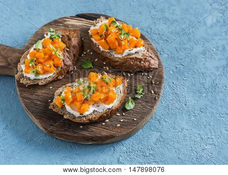 Pumpkin and goat's cheese bruschetta on a wooden cutting board on blue background. Healthy vegetarian snack