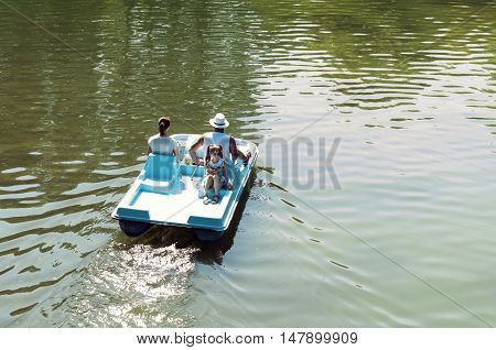 Bucharest, ROMANIA - August 21 2016: Chic young lady and her parents on a boat on a Sunday afternoon. Family relaxing in the park. BUCHAREST -August 21 2016