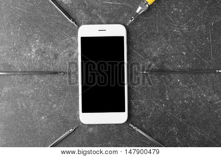 Mobile phone, screwdriver and exchangeable bits on grey background