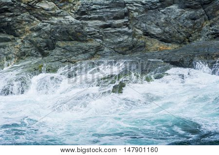 Waves crashing on rocks at Constantine Bay in Cornwall UK.