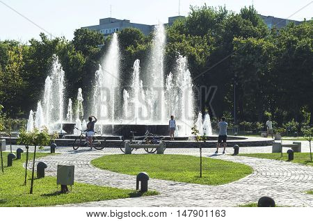 Bucharest, ROMANIA - August 21 2016: People relaxing near the fountain in Alexandru Ioan Cuza park or IOR park on a Sunday afternoon. BUCHAREST -August 21 2016