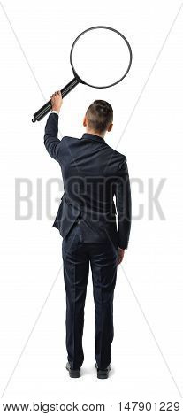 Back view of a businessman holding big magnifying glass in his outstretched arm isolated on white background. Exploration and research. Enlarging and searching.