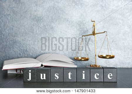 Wooden cubes with word JUSTICE and scales on a table