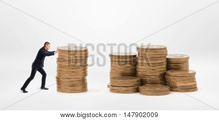 Side view of small businessman pushing a stack of golden coins to another stacks. Making a fortune. Earning money. Wealth and savings.