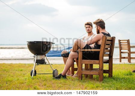 Two handsome young men frying meet on barbeque grill and talking outdoors