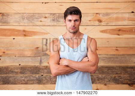 Serious attractive young man standing with arms crossed over wooden background