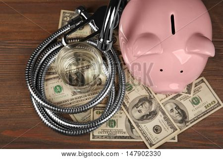 Pink piggy bank, glass of water, tap, hose and dollars on wooden background. Saving water concept
