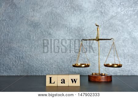 Wooden cubes with word LAW and scales on a table