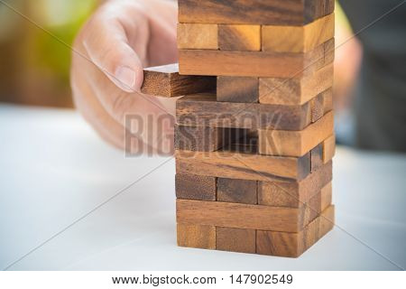 Close-up Of Asian Business Man's Hand Playing Wood Blocks Stack Game