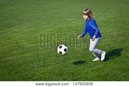 Boy playing soccer in the park - Authentic action with soccer ball - copy space right and left - landscape format