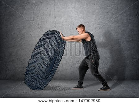 Side view of muscled young man pushing drawn tire to build strength. Crossfit and workout. Strong and handsome athlete.