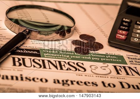 Close-up of Financial Figures, Business Newspaper, Coins, Calculator and Magnifying Glass
