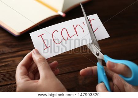 Hand cutting phrase I CAN'T on wooden background
