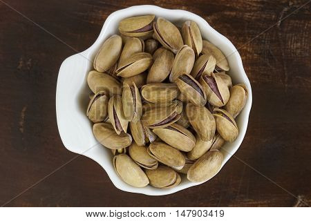 Pistachios in a white mussel-shaped porcelain bowl