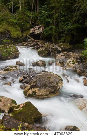Fast mountain river flowing among mossy stones and boulders in green forest.