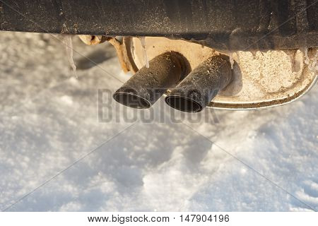 Car exhaust pipes with ice covering them